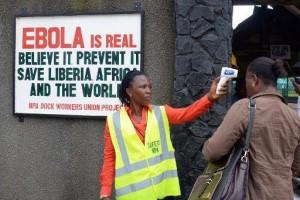 Operatore Sanitaria misura la temperatura corporea ad una passante. Alle spalle un cartello segnala la pericolosità del virus. Monrovia, Liberia.